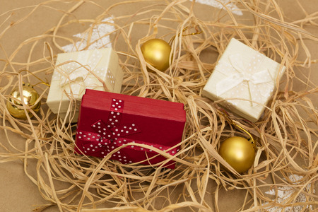 Christmas composition – gift boxes and gold ornaments on handmade background. Close-up.