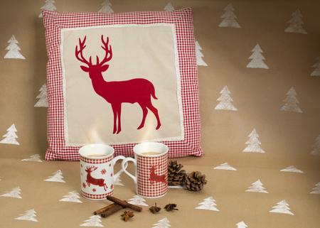 Christmaas composition – mugs and cushion with deer motive, cinnamon sticks and pinecones besides. 版權商用圖片