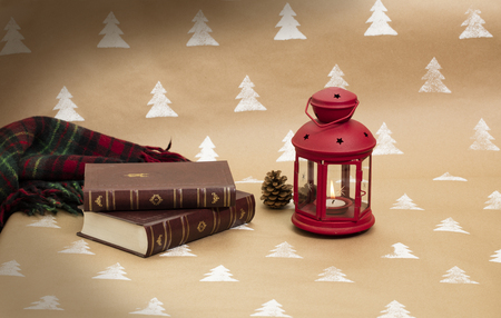 Christmas composition – red lantern, books and blanket.