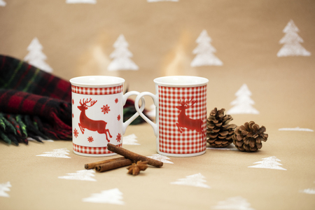Christmas composition – mugs with deer motive. Cinnamon sticks, anise, pinecones and plaid blanket in the background.