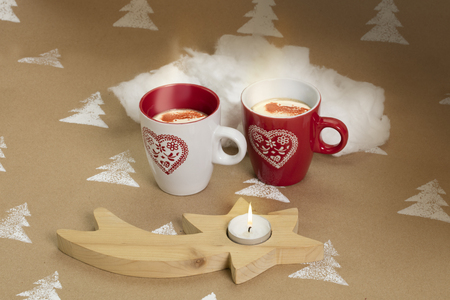 Christmas composition on handmade background – white & red mugs filled with drink, wooden star candle stand.