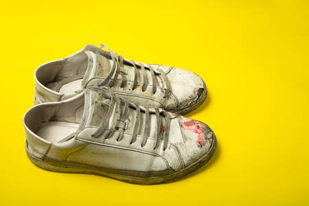 Dirty shoes, vintage white torn sneakers isolated on a yellow background.