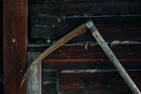 A rusty old metal braid hangs on a wooden wall