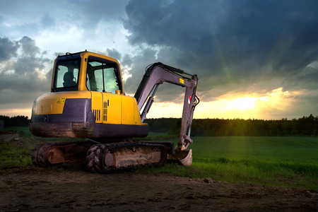 Yellow excavator standing on a construction site facing a green field in a sunset