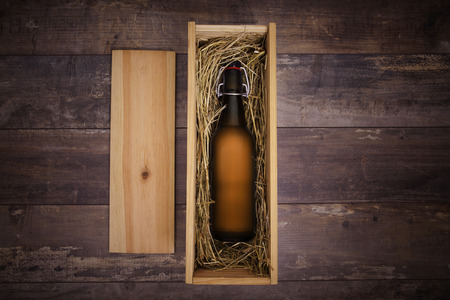 Craft beer bottle in a wooden gift box on a rustic table Foto de archivo