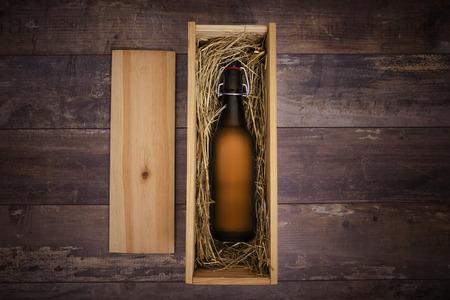 botellas de cerveza: Botella de cerveza artesanal en una caja de regalo de madera sobre una mesa rústica Foto de archivo