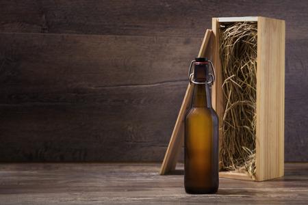 botellas de cerveza: Botella de cerveza artesanal con una caja de regalo de madera sobre una mesa r�stica