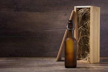Craft beer bottle with a wooden gift box on a rustic table