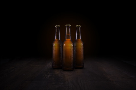 Three beer bottles on a rustic table