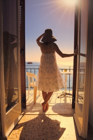 hotel balcony: A young woman seen from the back gazing at the sea on the balcony of a hotel Stock Photo