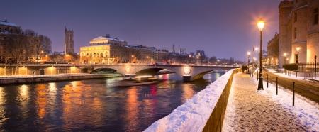 paris night: Quayside along River Seine under snow