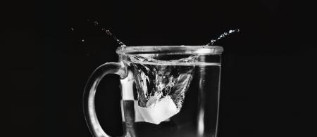 Zollette di zucchero che cade in una tazza trasparente pieno d'acqua Archivio Fotografico