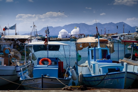 Fishing boats in Aegina harbor with little white orthodox church in the background