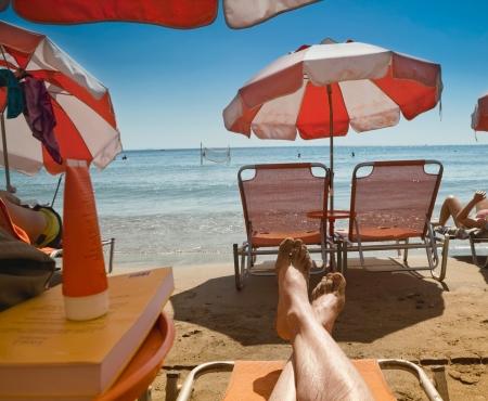 Le gambe di un uomo di prendere il sole su una sedia a sdraio su una spiaggia in Grecia