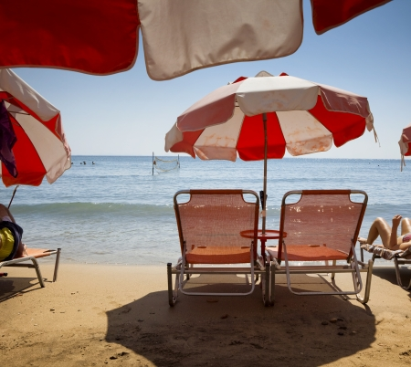 red chair: Beach chair on a public beach in Aegina island, Greece Stock Photo