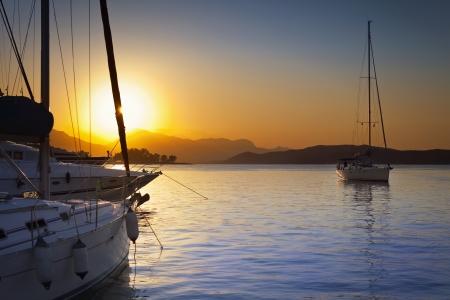 Vela navi nel porto di Poros in Grecia al tramonto