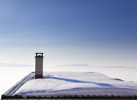 Roof covered with snow in the Alps mountains, above the clouds