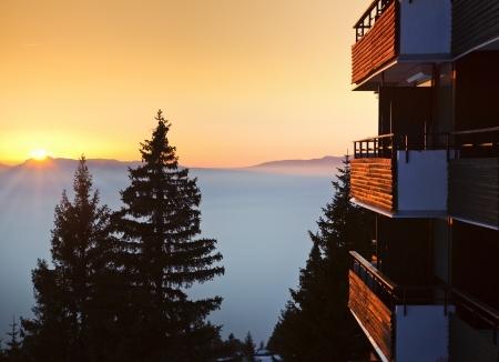 Edificio di legno in una stazione sciistica sulle Alpi al tramonto Archivio Fotografico