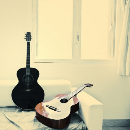 Two acoustic guitars in a white apartment