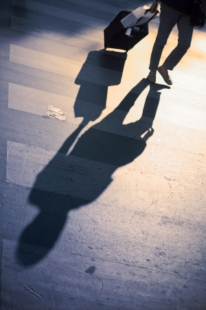 Legs of a woman crossing the street and pulling a suitcase Stock Photo