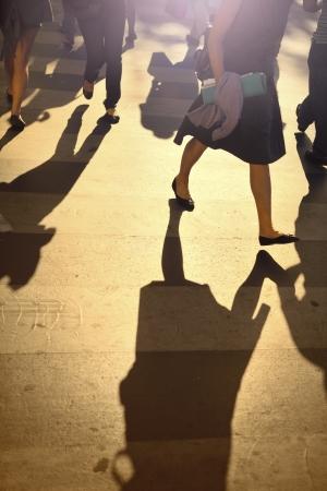 crossing legs: Legs of people crossing the street in Paris at sunset Stock Photo