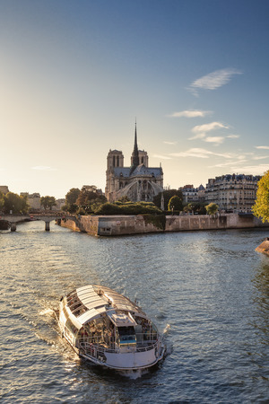 Notre Dame cathedral and sightseeing boat in Paris, France