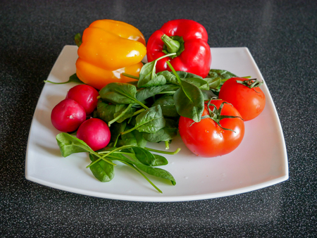 Fresh green vegetable salad with radish, tomatoes, color peppers on the white plate Stock Photo