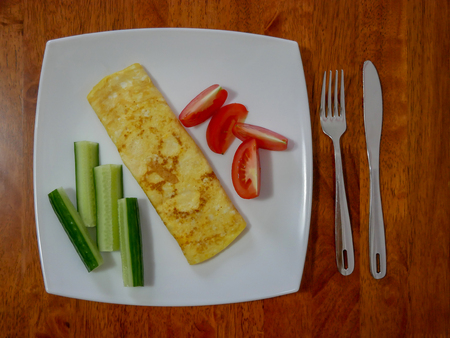 Classic omelet with tomatoes and cucumbers on the white plate. Fresh breakfast. Banco de Imagens