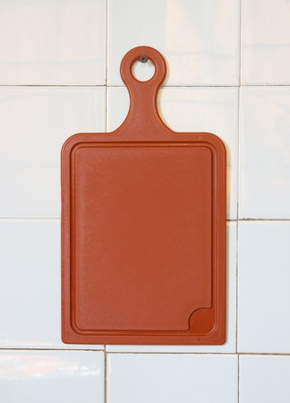 chopping: Plastic chopping board hanging on a wall.