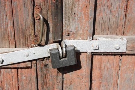 The big padlock hangs on an old door. photo