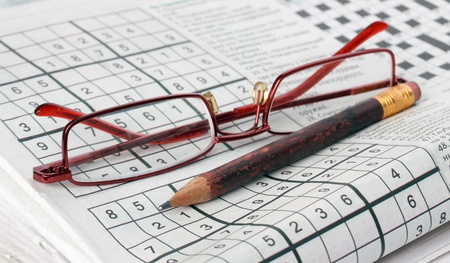 crossword puzzle: Pencil and glasses on the newspaper with a sudoku game.