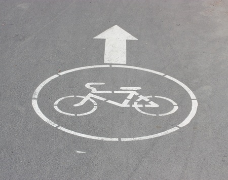 White arrow and sign a bicycle on asphalt. photo