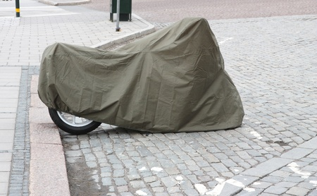 bike cover: Motorcycle in a cover on a city street.
