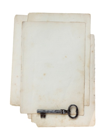 Old paper and key isolated on a white background. Foto de archivo