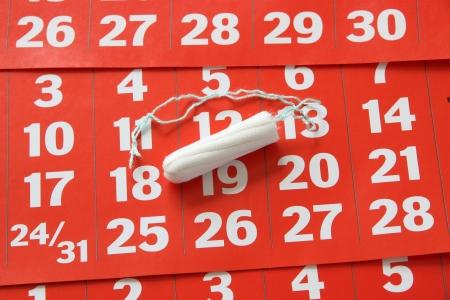tampon: El tamp�n sanitario tendido en un calendario de color rojo. Foto de archivo