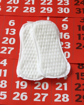 The sanitary napkin lying on a red calendar. Stock Photo