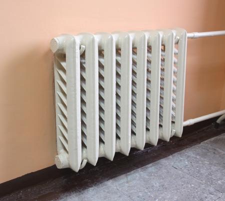 Verwarming radiator op roze muur in een kamer. Stockfoto