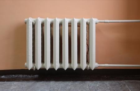 Verwarming radiator op roze muur in een kamer Stockfoto