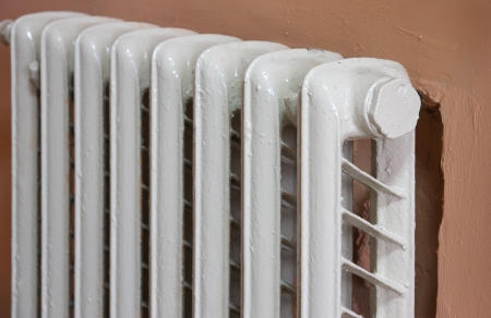 Heating radiator on pink wall in a room. 版權商用圖片