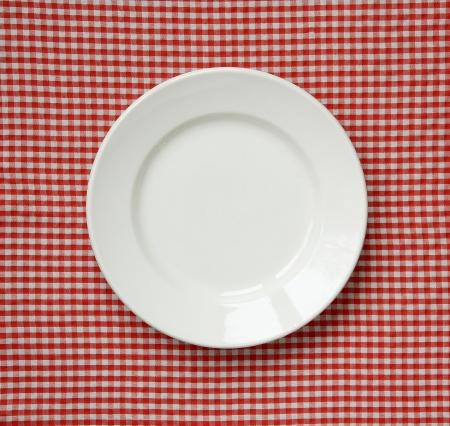checker plate: White ceramic plate on a checkered cloth. Stock Photo