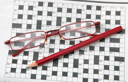 Potlood en een bril op de krant met een kruiswoordraadsel. Stockfoto
