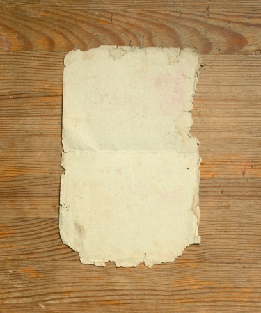 books on a wooden surface: Old sheet of paper on a wooden background. Stock Photo