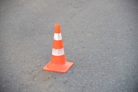 traffic cone: Striped orange cones on the asphalt road.