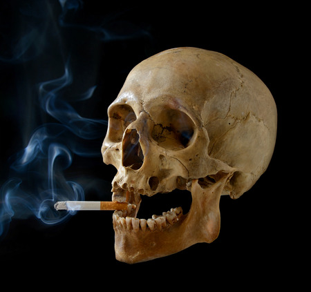Human skull smoking a cigarette on a black background. Stock Photo