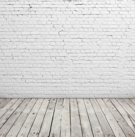 backdrop: Old white brick wall and wood floor.