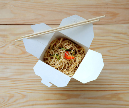 away: Chinese noodles in takeaway box on wooden background.