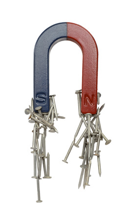 Magneet en spijkers geïsoleerd op een witte achtergrond. Stockfoto