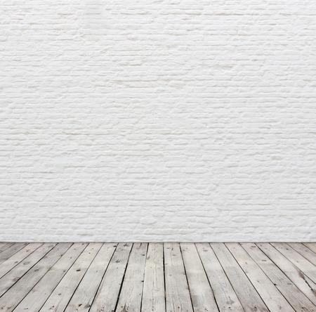 Oude witte bakstenen muur en houten vloer.