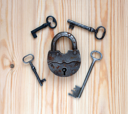 Padlock and keys on a wooden background.