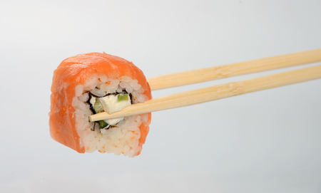 hashi: Sushi with red fish in bamboo chopsticks.